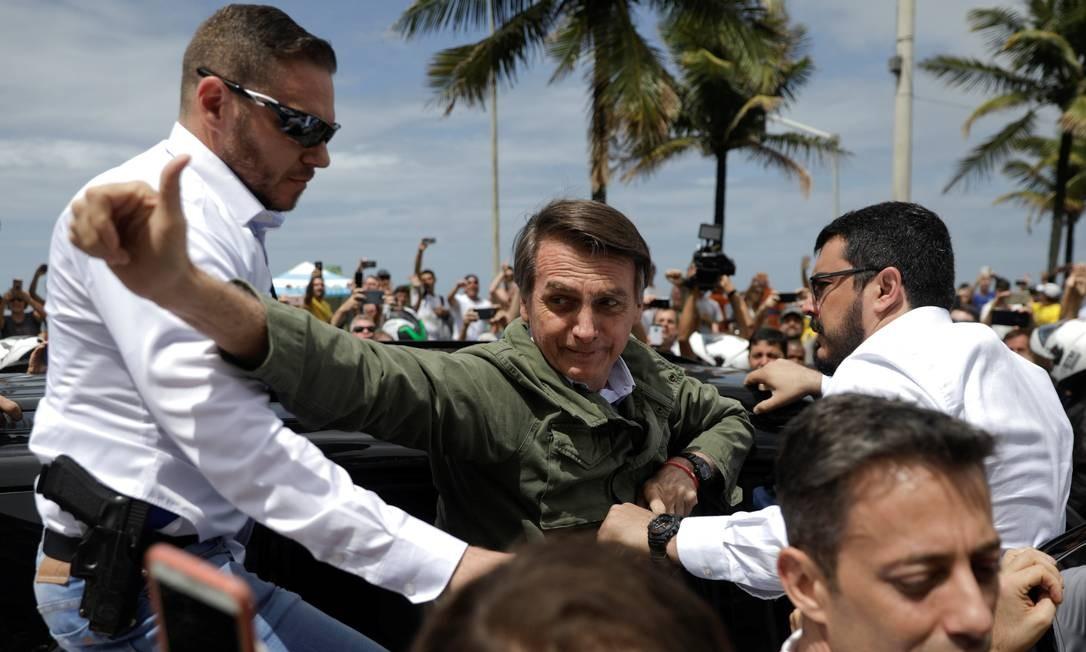 O presidenciável sai de casa para votar rodeado por seguranças Foto: Ricardo Moraes / Reuters