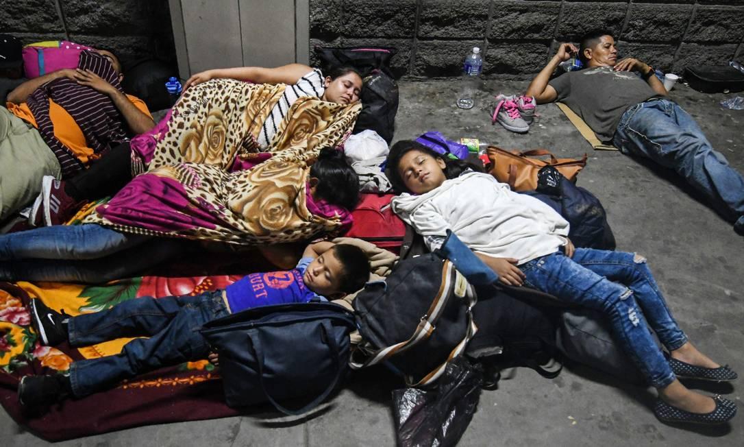 Família hondurenha dorme em rodoviária na noite anterior à partida da caravana migrante centro-americana da cidade de San Pedro Sula rumo aos EUA Foto: ORLANDO SIERRA / AFP