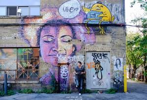 Visitante diante de um dos muitos painéis de grafite em Toronto, uma referência em arte de rua no mundo Foto: Kirsten Alana