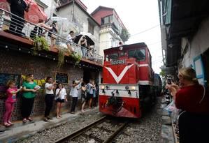 Pontualidade: o trem passa pela pequena rua de Hanói às 13h e às 19h atraindo a atenção dos turistas Foto: NHAC NGUYEN / AFP