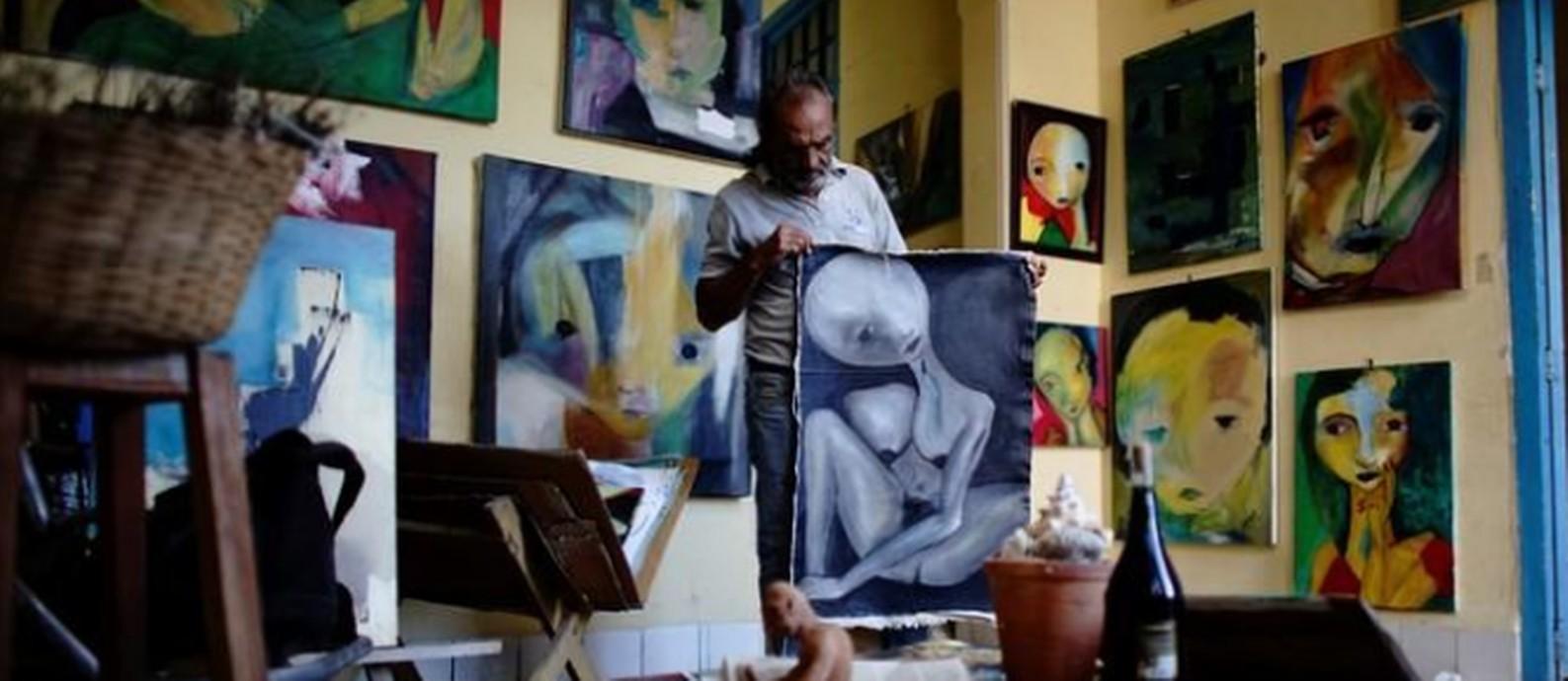 O pintor Roberto Loeje em meio a suas obras em seu ateliê em Havana Foto: Alexandre Meneghini / Reuters