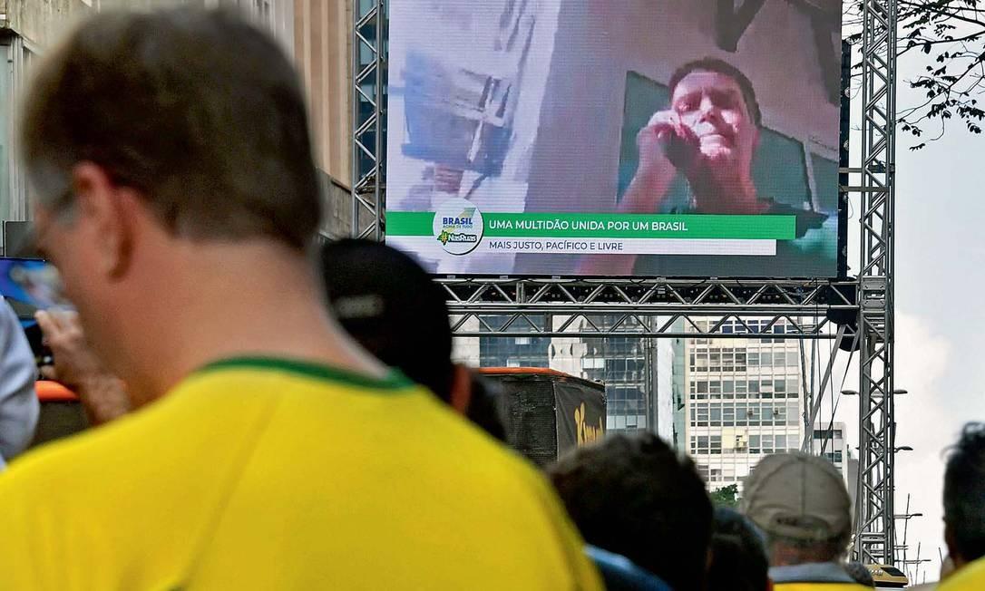 Na Avenida Paulista, apoiadores de Bolsonaro acompanham o discurso no qual prometeu cortar a verba publicitária de seu governo Foto: NELSON ALMEIDA/AFP