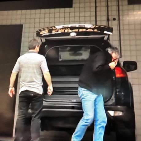 Pedro Paulo esconde o rosto ao ser levado por policiais federais Foto: Reprodução / TV Globo