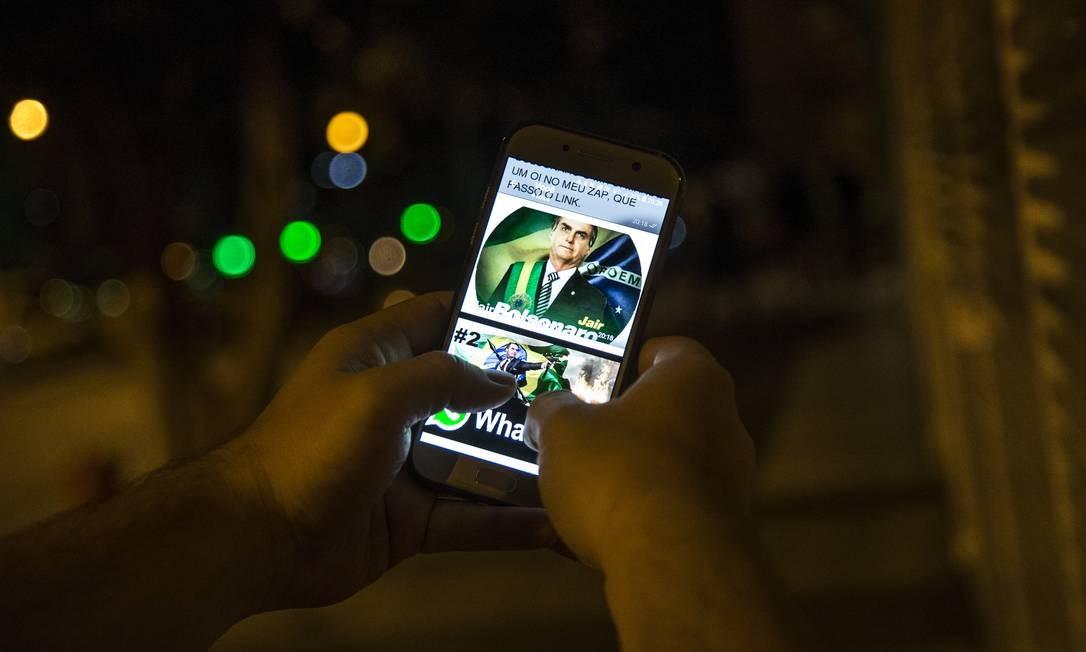 Imagem do Presidente eleito Jair Bolsonaro em celular Foto: Guito Moreto / Agência O Globo