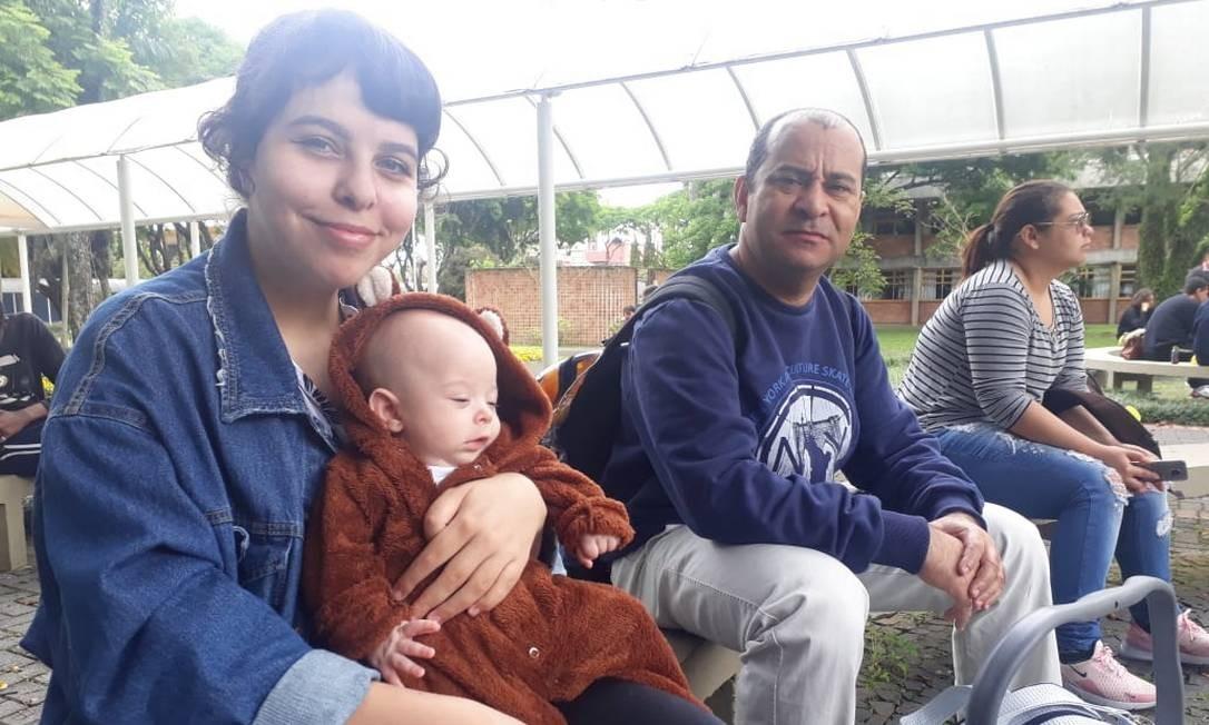 Luiza Hamann, de 20 anos, segura no colo o filho Leo. O pai da jovem, Adenilson, a acompanhou na prova, ficando com o bebê em uma sala separada Foto: Christianne Machiavelli/04-11-2018