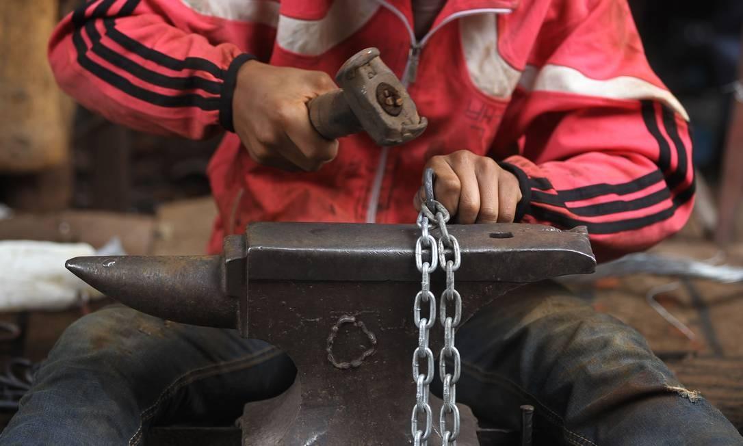 Homem trabalha em indústria de correntes de ferro na capital Bagdá Foto: AHMAD AL-RUBAYE / AFP