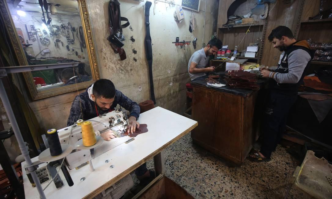 Iraquianos trabalham em oficina de cintos de couro na capital Bagdá Foto: AHMAD AL-RUBAYE / AFP