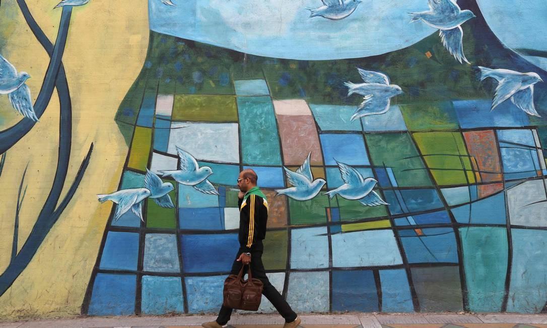 Iraniano passa por muros coloridos na capital Teerã, Irã Foto: ATTA KENARE / AFP