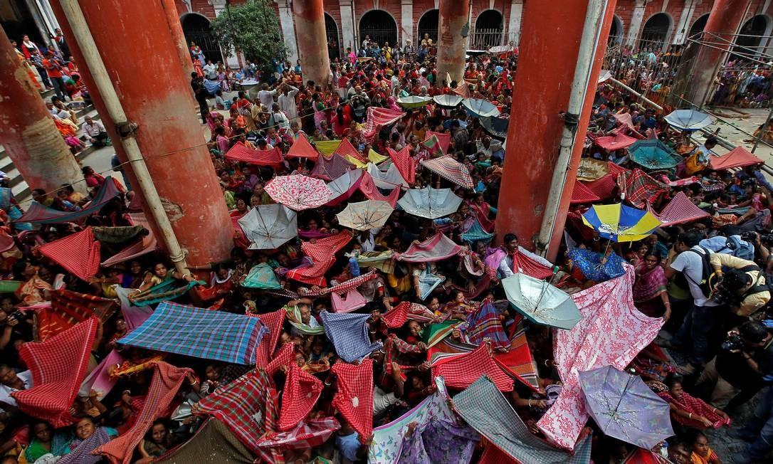 Devotos hindus seguram guarda-chuvas para receber arroz durante o festival de Annakut em Calcutá, Índia Foto: RUPAK DE CHOWDHURI / REUTERS