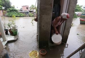 Dona Irene da Silva Reis tenta tirar a água que invadiu sua casa Foto: Cléber Júnior / Agência O Globo