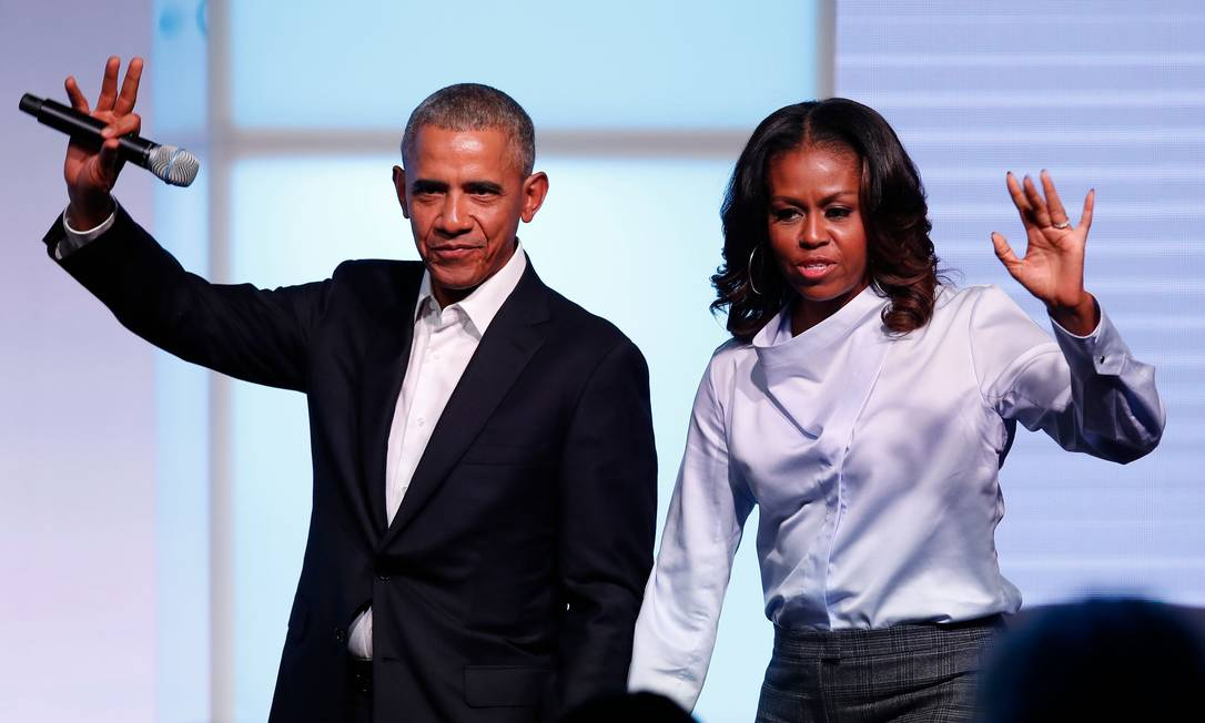Barack e Michelle Obama acenam para público em cúpula de fundação, em Chicago Foto: JIM YOUNG / AFP