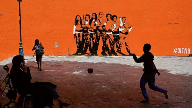 Garoto joga futebol diante de mural que anuncia temporada da série Orange is the new black, da Netflix Foto: CHRISTOPHE ARCHAMBAULT / AFP