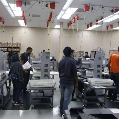 Funcionários eleitorais computam os votos em máquinas no condado de Broward, Flórida: recontagem Foto: JOE SKIPPER / AFP