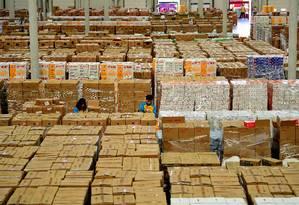 Bilhões em pacotes. Empregados trabalham no estoque para o Dia dos Solteiros em Shenyang, na China: mais de 200 mil varejistas participam este ano Foto: STR / AFP