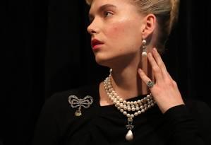 Modelo apresenta algumas das joias da rainha Maria Antonieta que irão a leilão quarta-feira, em Genebra. Na foto, um colar de pérolas e diamante; um broche de diamantes e um par de brincos de pérola e diamantes Foto: DANIEL LEAL-OLIVAS / AFP