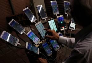 Chen San-yuan joga 'Pokémon Go' com 15 celulares Foto: TYRONE SIU / REUTERS