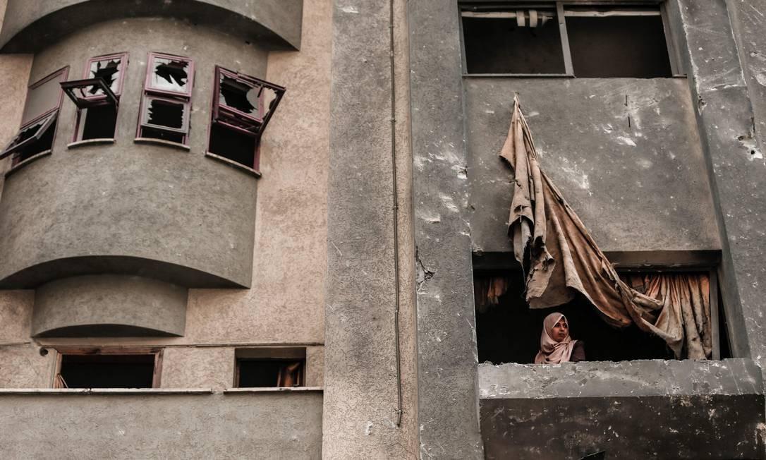 Palestina olha pela janela de um prédio, danificada por um ataque aéreo israelense no início desta semana na Faixa de Gaza Foto: MAHMUD HAMS / AFP