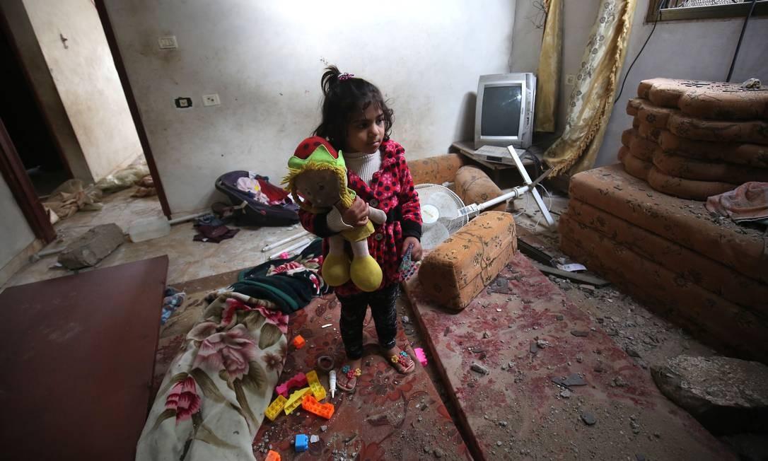 Uma jovem garota palestina segura um brinquedo danificado por ataque aéreo israelense esta semana em Rafah, no sul da Faixa de Gaza Foto: SAID KHATIB / AFP