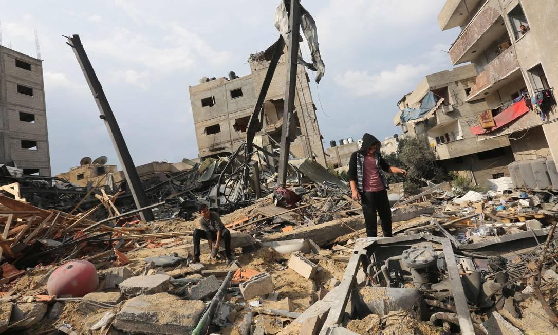 Palestinos em meio aos escombros do prédio da emissora de televisão Al-Aqsa, controlada pelo Hamas, destruída por um ataque aéreo israelense no início desta semana, na Faixa de Gaza em 14 de novembro de 2018. Foto: MAHMUD HAMS / AFP
