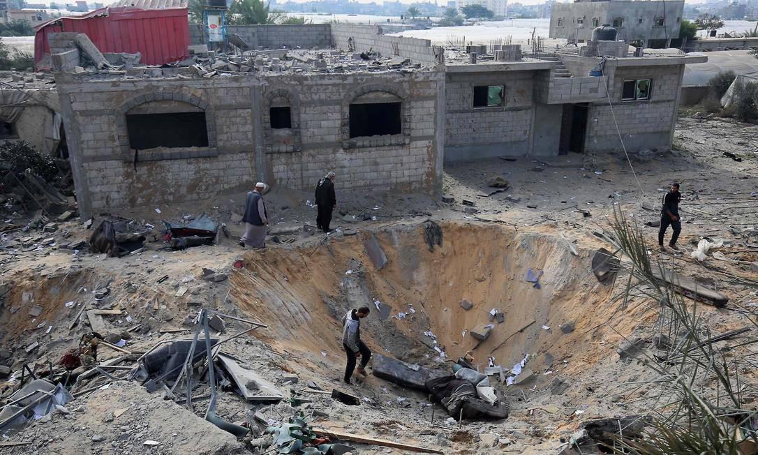 Palestinos inspecionam uma cratera causada por um ataque aéreo israelense, em Rafah, no sul da Faixa de Gaza Foto: SAID KHATIB / AFP