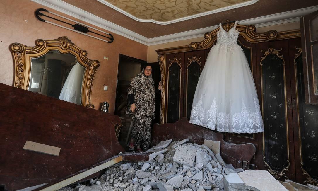 Uma palestina entra em um quarto destruído pelo ataque aéreo israelense Foto: MAHMUD HAMS / AFP
