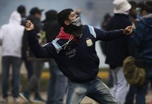 Manifestante atira pedra em policiais durante protesto contra o projeto de Orçamento para 2019 ao lado do Congresso argentino, em Buenos Aires Foto: Mario De Fina / NurPhoto via Getty Images