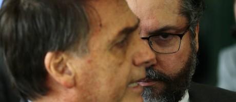 Nelso Ernesto Araújo, futuro ministro das Relações Exteriores, ao fundo, olha para o presidente-eleito Jair Bolsonaro Foto: Jorge William / Agência O Globo