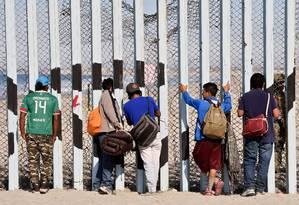 Migrantes centro-americanos contornam cerca que separa EUA e México em praia de Tijuana Foto: ALFREDO ESTRELLA / AFP