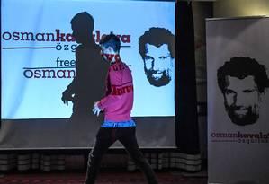 Homem passa em frente a tela mostrando foto do ativista Osman Kavala Foto: OZAN KOSE / AFP