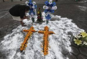Uma mulher monta cruzes de flores sobre local em que um linchamento aconteceu, na cidade de Ajalpan, México Foto: Marco Ugarte / AP
