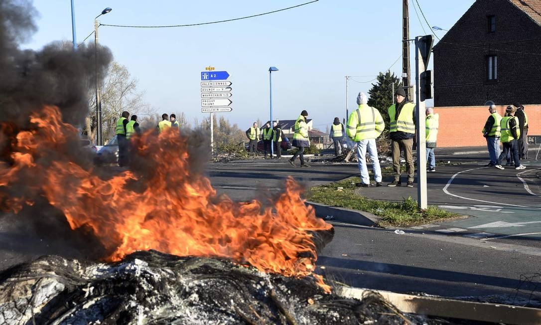 Intergrantes do movimento Coletes Amarelos (Gilets Jaunes) participam de bloqueio, no domingo, em uma rotatória em Douchy-les-Mines, perto de Valenciennes, norte da França, um dia depois de um protesto nacional contra os altos preços dos combustíveis. Foto: FRANCOIS LO PRESTI / AFP