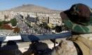 Militante houthi observa iemenitas em protesto em Sanaa Foto: Khaled Abdullah / REUTERS
