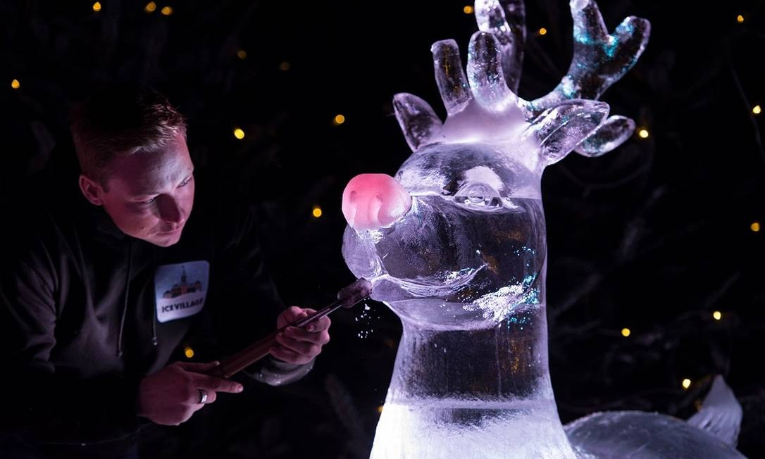 Escultor de gelo, Mark Hackney trabalha durante festival natalino na cidade de Manchester, na Inglaterra Foto: OLI SCARFF / AFP