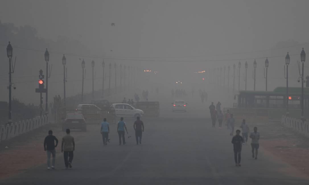 Pessoas caminham pelas ruas de Nova Délhi, com o ar extremamente poluído Foto: MONEY SHARMA / AFP/02-11-2018