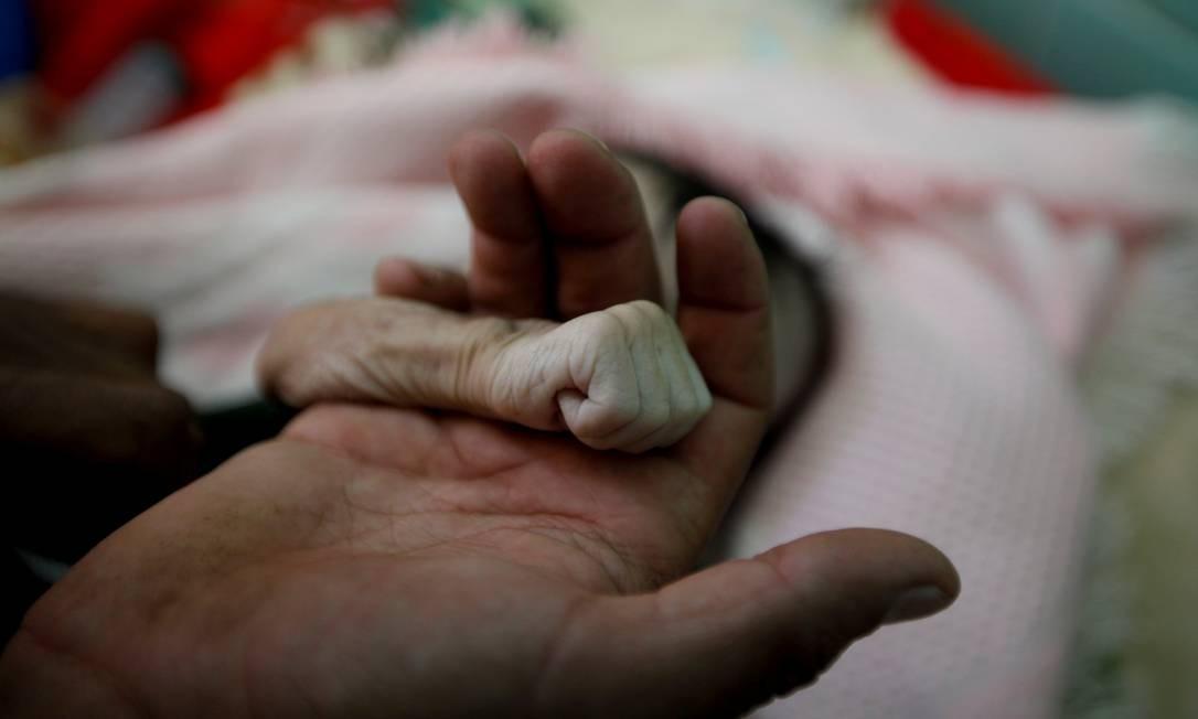 Pai segura a mão da filha Hajar, de 4 meses, morta por má nutrição em Sanaa, no Iêmen Foto: MOHAMED AL-SAYAGHI / REUTERS