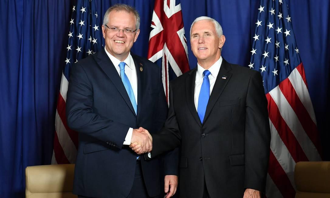 Premier da Austrália, Scott Morrison, e vice-presidente dos EUA, Mike Pence, apertam mãos em encontro de 17 de novembro de 2018; os dois países rejeitam a implementação do pacto mundial sobre migração da ONU Foto: SAEED KHAN / AFP