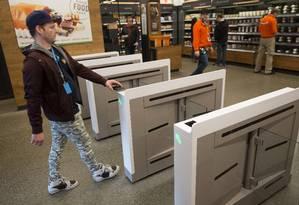 Na loja Amazon Go de Seattle, nos EUA, o cliente apenas escaneia seu celular numa catraca, pega os itens que deseja e sai. As compras são descontadas diretamente no cartão Foto: Mike Kane / Bloomberg