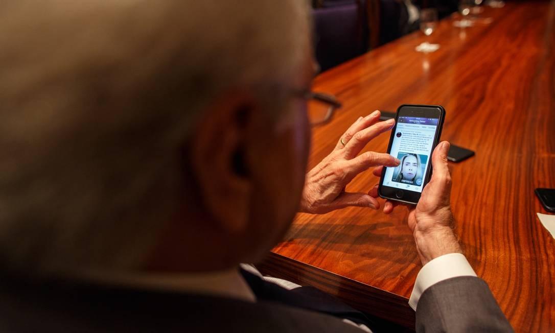 Temer vê no celular as postagens na conta em rede social que faz graça com sua autoestima Foto: Daniel Marenco / Agência O Globo