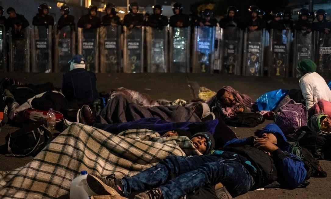 Grupo de centro-americanos descansam perto da fronteira entre EUA e México em El Chaparral, Tijuana Foto: GUILLERMO ARIAS / AFP