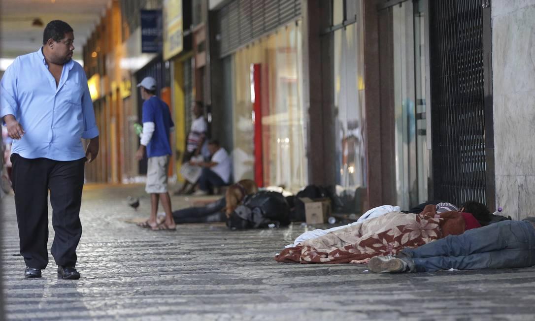 Desigualdade social. Homem observa grupo dormindo no calçadão da Avenida Amaral Peixoto, no Centro, um dos principais pontos de concentração de pessoas em situação de rua Foto: Márcio Alves / fotos de márcio alves
