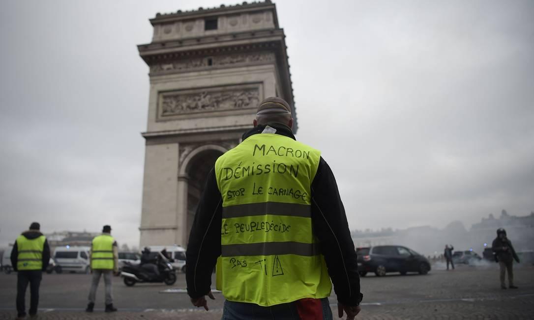 """Um manifestante do grupo colete amarelo com a inscrição """"renúncia de Macron"""", em frente ao Arco do Triunfo, na avenida dos Champs Elysées, em Paris Foto: LUCAS BARIOULET / AFP"""