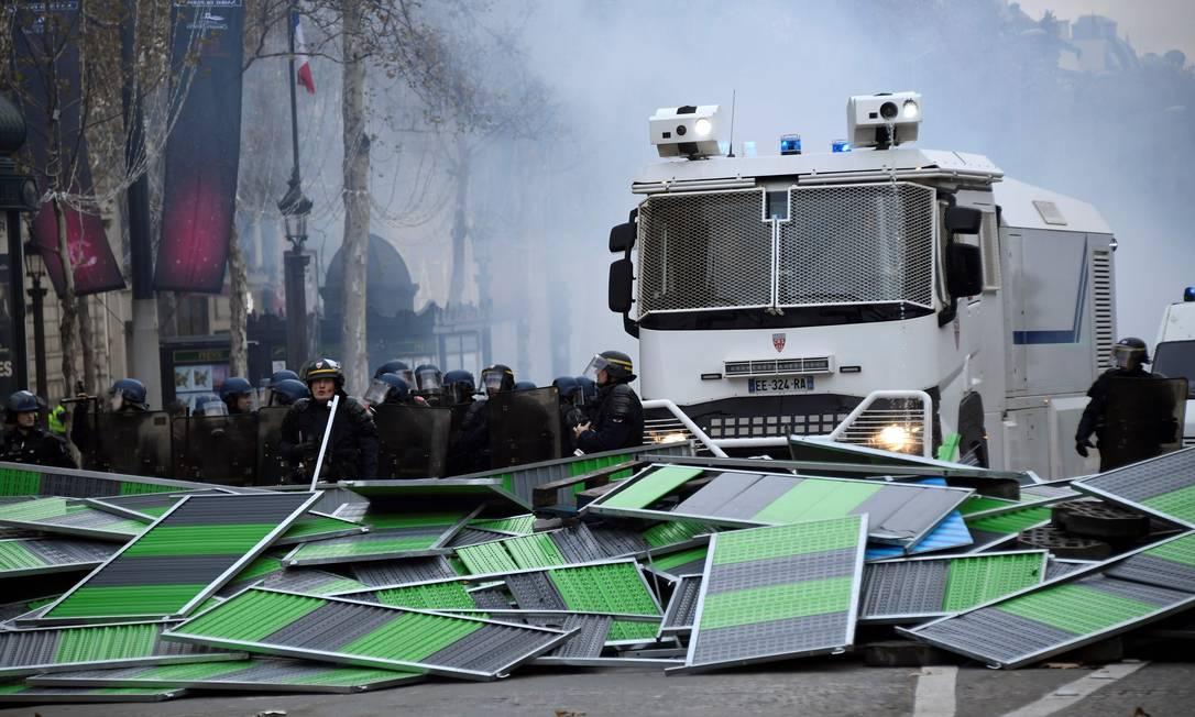 Integrantes da polícia antimotim se posicionam atrás de uma barricada durante um protesto dos coletes amarelos nos Champs-Elysées. A polícia disparou gás lacrimogêneo e canhões de água contra os manifestantes Foto: BERTRAND GUAY / AFP