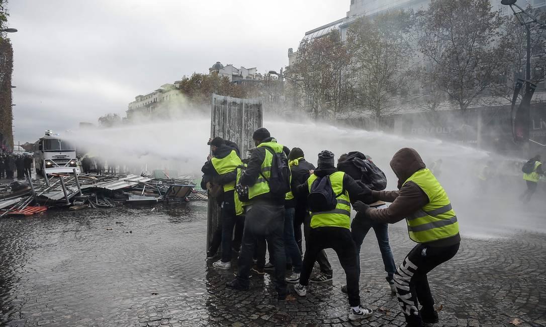 Manifestantes tentam se proteger dos jatos de água disparados pela polícia Foto: LUCAS BARIOULET / AFP