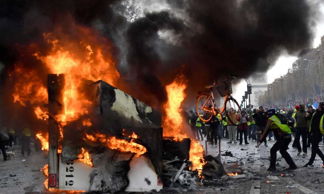 Um homem joga uma bicicleta em direção a um caminhão queimado durante um protesto de coletes amarelos (Gilets jaunes) contra o aumento dos preços do petróleo e custos de vida perto do Arco do Triunfo Foto: BERTRAND GUAY / AFP