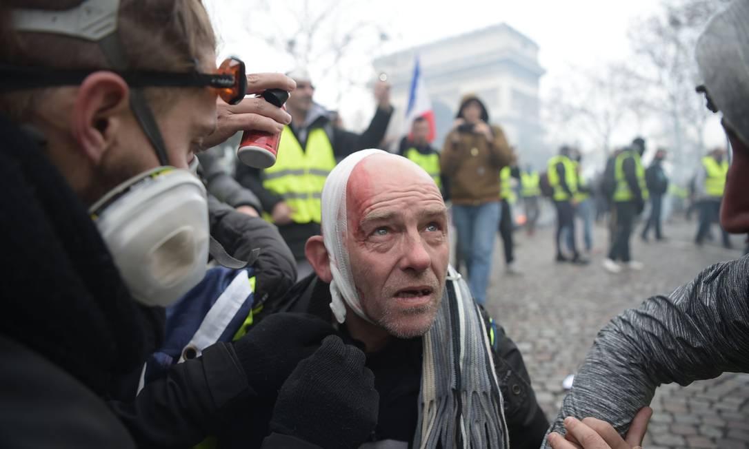 Manifestante do grupo dos 'coletes amarelos' é ferido durante o protesto nos Champs-Elysées, em Paris. Policiais e manifestantes entraram em confronto durante o protesto na manhã de sábado, na capital francesa Foto: LUCAS BARIOULET / AFP