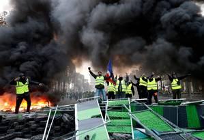 Descontentamento. Coletes amarelos gritam slogans contra o governo Macron numa barricada improvisada junto ao Arco do Triunfo, na Avenidas dos Champs-Elysées, em Paris: proliferação de grupos a partir de uma petição na internet Foto: FRANCOIS GUILLOT / FRANCOIS GUILLOT/AFP