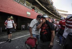 Torcedores do River protegem o nariz após lançamento de gás de pimenta Foto: JAVIER GONZALEZ TOLEDO / AFP