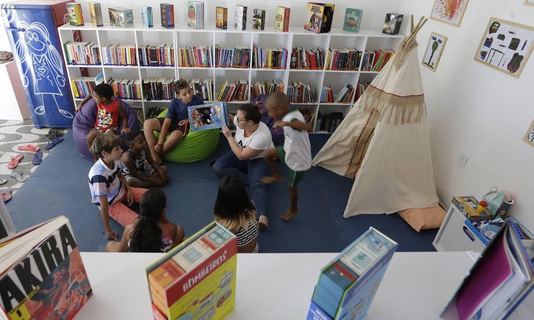 Encantamento. Crianças acompanham história no Canto de Leitura da comunidade Campo Belo, em Nova Iguaçu: projeto voltado para público infantojuvenil Foto: Antonio Scorza / Agência O Globo