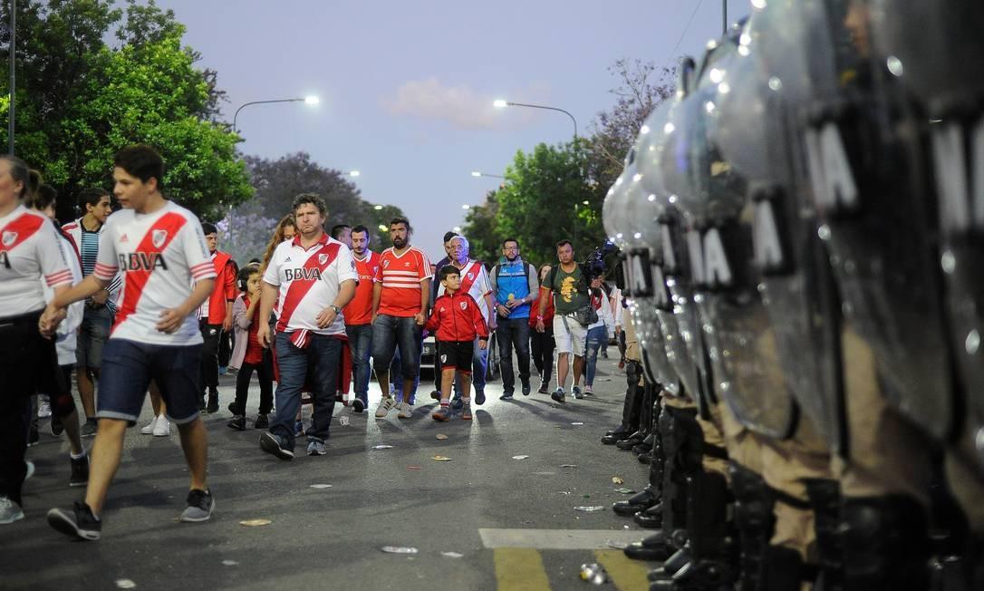 Torcedores do River Plate deixam o estádio à frente da polícia Foto: JAVIER GONZALEZ TOLEDO / AFP