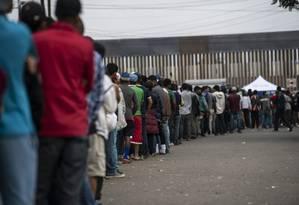 Migrantes centro-americanos fazem fila para conseguir alimentos nos arredores de um acampamento ao lado da fronteira entre EUA e México em Tijuana, 24 de novembro de 2018 Foto: AFP / Pedro PARDO